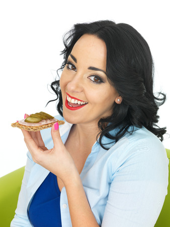 german sausage: Young Healthy Woman Eating a Cracker with German Sausage and Gherkin
