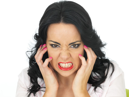 clenching teeth: Portrait of an Angry Frustrated Young Hispanic Woman in Her Twenties Clenching Her Teeth Stock Photo