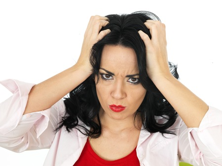 pulling beautiful: Portrait of a Frustrated Beautiful Young Hispanic Woman in Her Twenties Pulling Her Hair in Disbelief Stock Photo