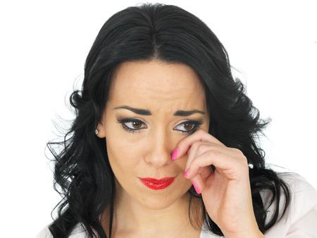 tearful: Portrait of a Beautiful Young Hispanic Woman in Her Twenties Wiping Her Eye Looking Upset