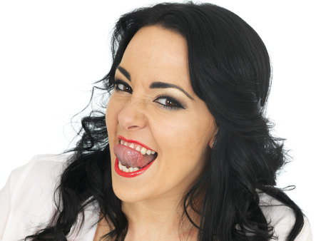 close out: Cheeky Beautiful Young Hispanic Woman in Her Twenties Pulling Silly Faces and Sticking Out Her Tongue