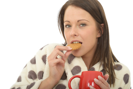 tea cosy: Attractive Young Woman In Her Twenties Wearing A Warm Cosy Dresssing Gown Enjoying Tea and Biscuits Stock Photo