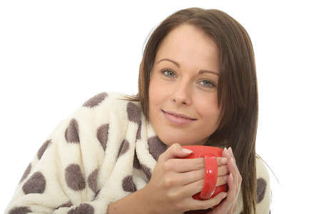 tea cosy: Attractive Young Woman In Her Twenties Holding and Enjoying A Cup Of Tea In Her Warm Cosy Dressing Gown