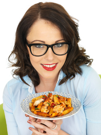 Pretty Young Woman in Her Twenties Wearing Black Framed Glasses Holding and Eating Penne Pasta photo