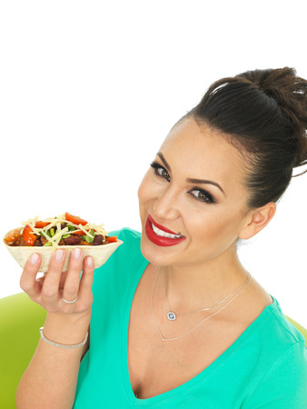 low cut: Beautiful Attractive Young Hispanic Woman With Soft Chille Beef Taco with Salad and Grated Cheese