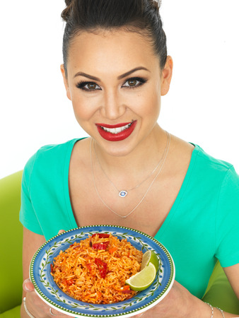 low cut: Beautiful Young Hispanic Woman Holding A Plate of Spicy Mexican Fried Rice With Fresh Lime Against A White Background