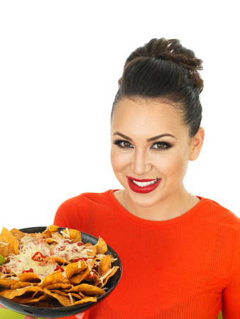 cheesy: Beautiful Young Hispanic Woman With a Plate of Cheesy Nachos and Spicy Salsa Sauce Against A White Background Stock Photo