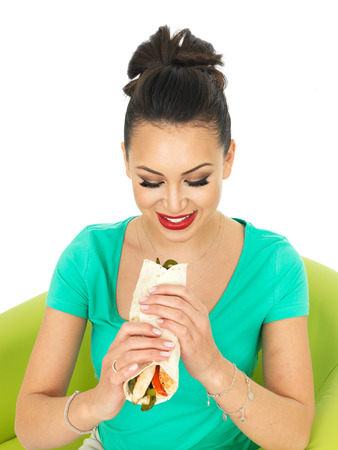 low cut: Beautiful Attractive Young Hispanic Woman With A Chicken Fajita Wrap and Sliced Peppers Against A White Background