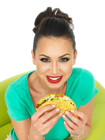 low cut: Beautiful Young Hispanic Woman With Crispy Chilli Beef Tacos with Salad and Grated Cheese Against A White Background
