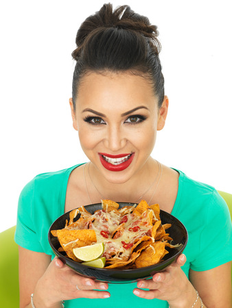 cheesy: Beautiful Attractive Young Hispanic Woman With Cheesy Nachos and a Spicy Salsa Sauce With Chilli