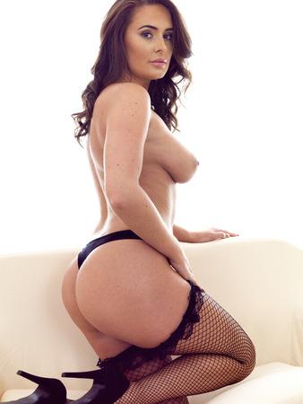 Mujer hispana en topless atractiva hermosa joven en Mallas Medias de unos veinte años contra un fondo blanco Foto de archivo