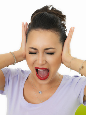 bad temper: Portrait Of A Beautiful Young Hispanic Woman In Her Twenties Covering Her Ears To Block Out Noise and Sound Stock Photo