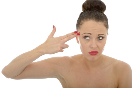 holding gun to head: Beautiful Young Caucasian Woman Gesturing As If Holding A Gun To Her Head With Her Hand And Fingers Against White