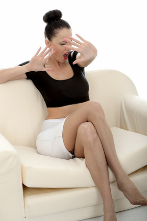 tight fitting: Portrait Of A Beautiful Attractive Young Caucasian Woman Posing On A Sofa Or Couch Fending Off Looking Scared anf Frightened Holding Hand Up In Defence Stock Photo