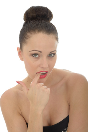 coy: Attractive Young Woman With A Finger In Her Mouth Looking Innocent Shy and Coy Wearing A Black Dress Against White Stock Photo
