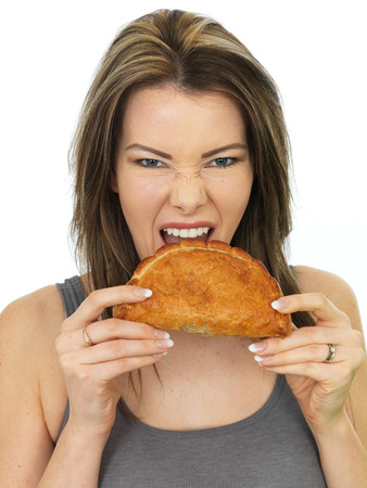 pasty: Attractive Happy Young Woman Eating a Baked Cornish Pasty