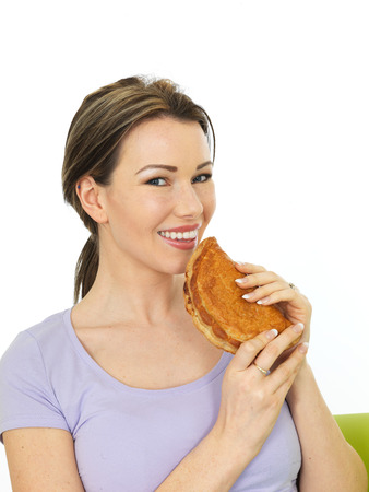 pasty: Attractive Happy Young Woman Holding a Traditional British Baked Fresh Cornish Pasty