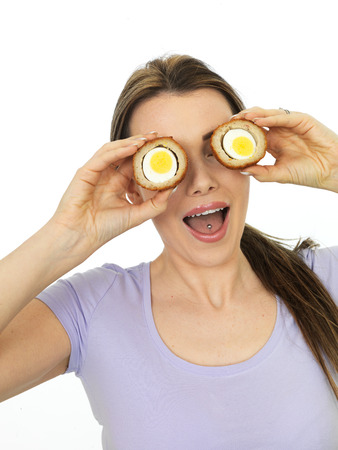 daft: Attractive Playful Young Woman Holding A Cut Scotch Egg