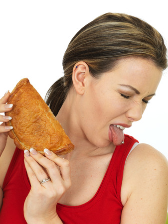 pasty: Attractive Young Woman Dislikes Holding a Cooked Cornish Pasty Savory Snack Stock Photo