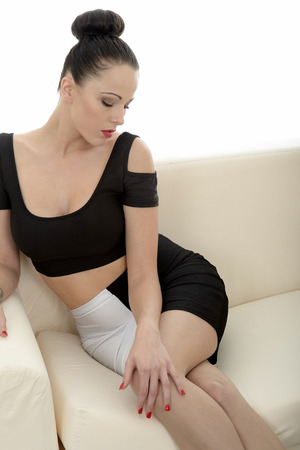 tight fitting: Portrait Of A Beautiful Attractive Young Caucasian Woman Relaxing And Posing On A Sofa Or Couch Teasing And Looking Very Seductive Stock Photo