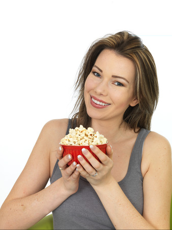 vest top: Attractive Happy Young Caucasian Woman Eating and Enjoying a Bowl of Popcorn Wearing A Grey Vest Top Shot Against White Stock Photo