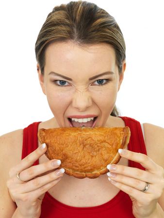 pasty: Attractive Young Woman Eating a Cooked Cornish Pasty Savory Snack