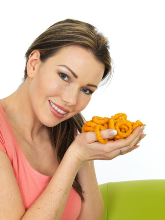 flavoured: Attractive Smiling Young Woman Holding A Handful Of Onion Flavoured Rings Snacks