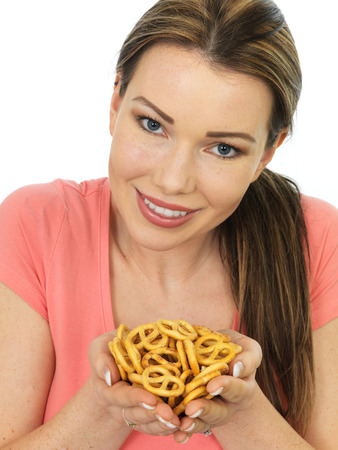 nibbles: Attractive Happy Smiling Young Woman Holding A Handful Of Salted Pretzels