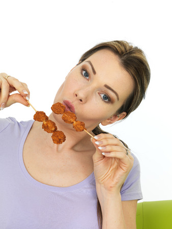 asian style: Attractive Young Woman Holding Two Spicy Asian Style Chicken Satay Sticks