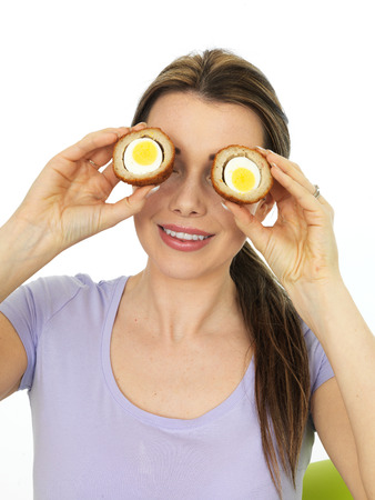 scotch: Attractive Playful Young Woman Holding A Cut Scotch Egg