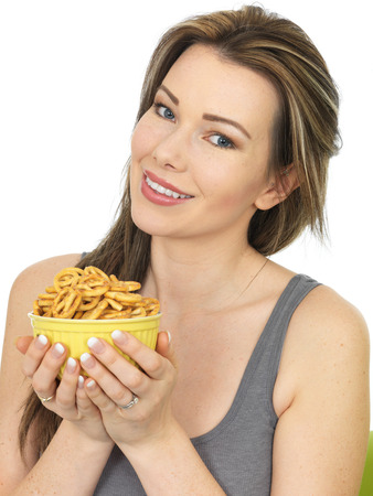 nibbles: Attractive Happy Young Woman Holding a Bowl of Salted Pretzel Snacks
