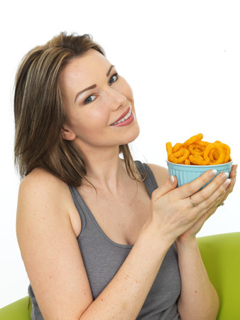 flavoured: Attractive Happy Young Woman Holding a Bowl of Onion Ring Flavoured Snacks Stock Photo