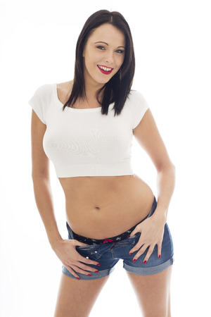 vest top: Sexy Young Caucasian Woman Wearing a White Vest Top and Blue Denim Shorts Posing Pin Up Against A White Background