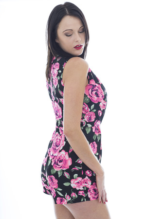 demure: Attractive Sexy Young Woman Wearing a Short Floral Playsuit Shot Against A White Background Showing Cleavage