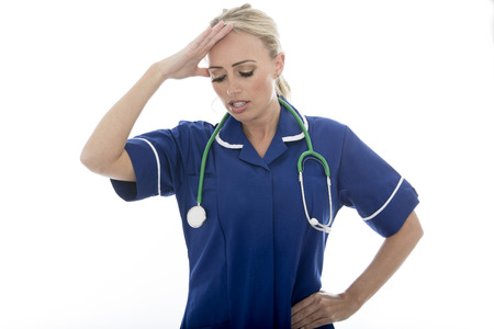 Attractive Young Woman Posing As A Doctor or Nurse In Theatre Scrubs With A Stethoscope Isolated against a Plain White Background Stock Photo