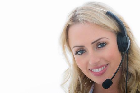 흰색 배경에 대해 클라이언트를 호출하는 전화 헤드셋을 사용하여 매력적인 젊은 비즈니스 여성