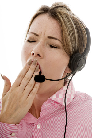 over worked: Tired Attractive Young Business Woman Using a Telephone Headset Making Sales Calls or Marketing Against a Plain White Background Yawning