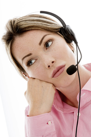 miserable: Bored Attractive Young Business Woman Using a Telephone Headset Making Sales Calls or Marketing Against a Plain White Background