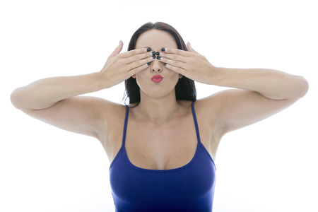 pulling faces: Attractive Young Woman Covering Her Eyes Pulling Faces Isolated Against a White Background