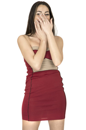 mini dress: Attractive Young Woman Covering Her Mouth Laughing Wearing A Sexy Short Red Mini Dress Stock Photo