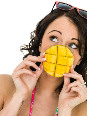 heathy diet: Healthy Young Woman Holding A Piece Of Mango Fruit Isolated Against A White Backgorund