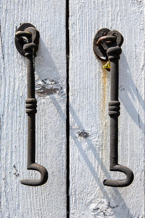 restraints: Two Steel Hooks Hanging Off a White Painted Wooden Door Frame in Close Up Stock Photo