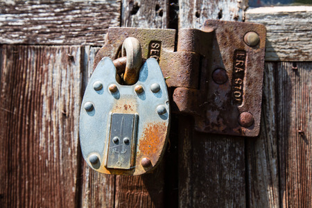 outbuilding: Rusting Locked Padlock On Weathered Old Wooden Doors