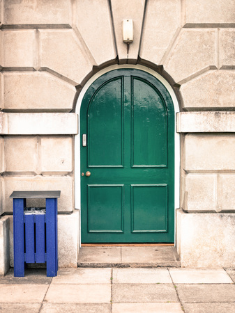 heavy set: Heavy Wooden Green Double Door Set in an Architectural Stone Archway With a Blue Waste Bin
