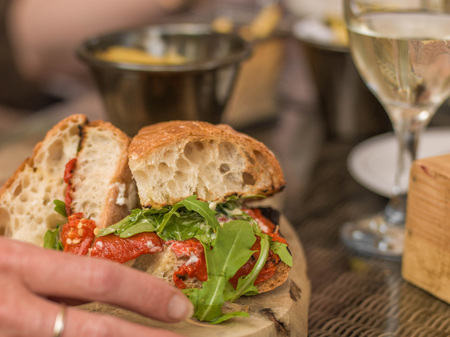 tight filled: Creative Tight Cropped Image of a Vegetarian Roast Pepper Ciabatta Bread Sandwich or Roll And White Wine