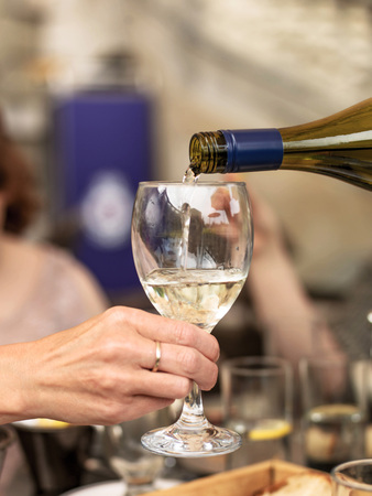 al fresco: Pouring White Wine into a Glass Held by a Hand in Close Up Against a Table Setting