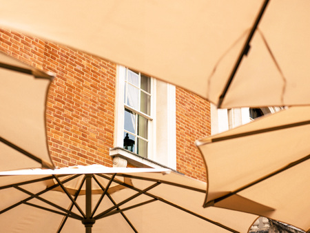 window shades: Open Parasols or Umbellas Creating a Pattern Against a Red Brick Wall of a Building
