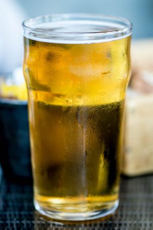 socializando: Vaso de una pinta de cerveza ligera o cerveza dorada en una tabla