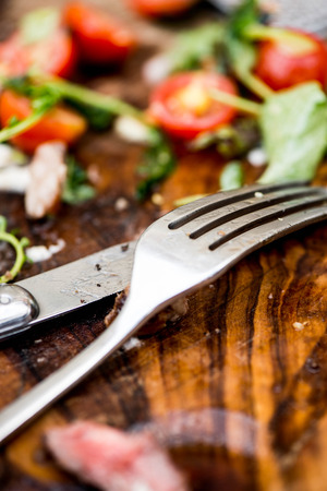 overs: Finished Meal on a Wooden Board With a Knife and Fork Stock Photo