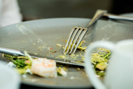 overs: Food Left Overs on a Plate With a Knife and Fork After Finishing a Meal Stock Photo